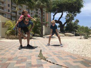 Family meeting an iguana in Aruba