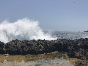 Wave crashing into lava rock in Aruba