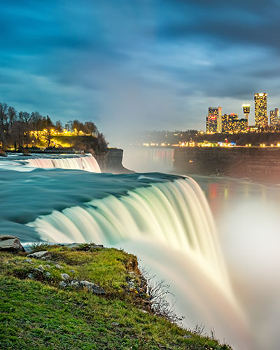 Long exposure photo of the American Falls waterfall in New York State, USA and the skyline of the city of Niagara Falls, Ontario, Canada, in the background, illuminated at twilight blue hour.