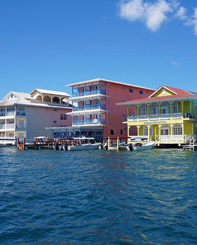 Colorful Caribbean buildings over the water with boats at dock, Colon island, Bocas del Toro, Panama