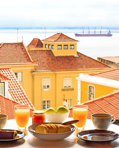 Romantic breakfast by window with a view in Lisbon, Portugal.