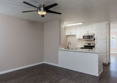 Empty living room with view into kitchen and entryway