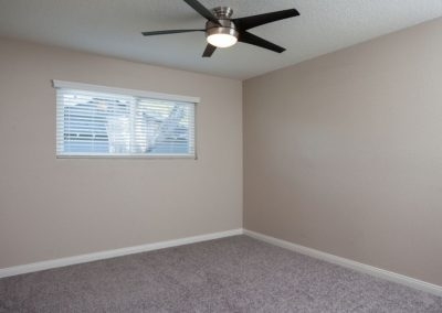 Empty bedroom with carpet, ceiling fan, and window