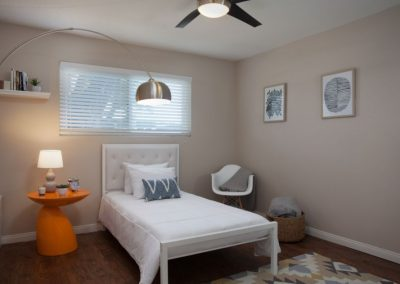 Furnished bedroom with window and ceiling fan