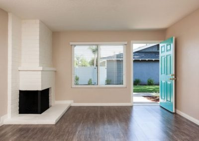 Living room with open blue door to outside and brick fireplace
