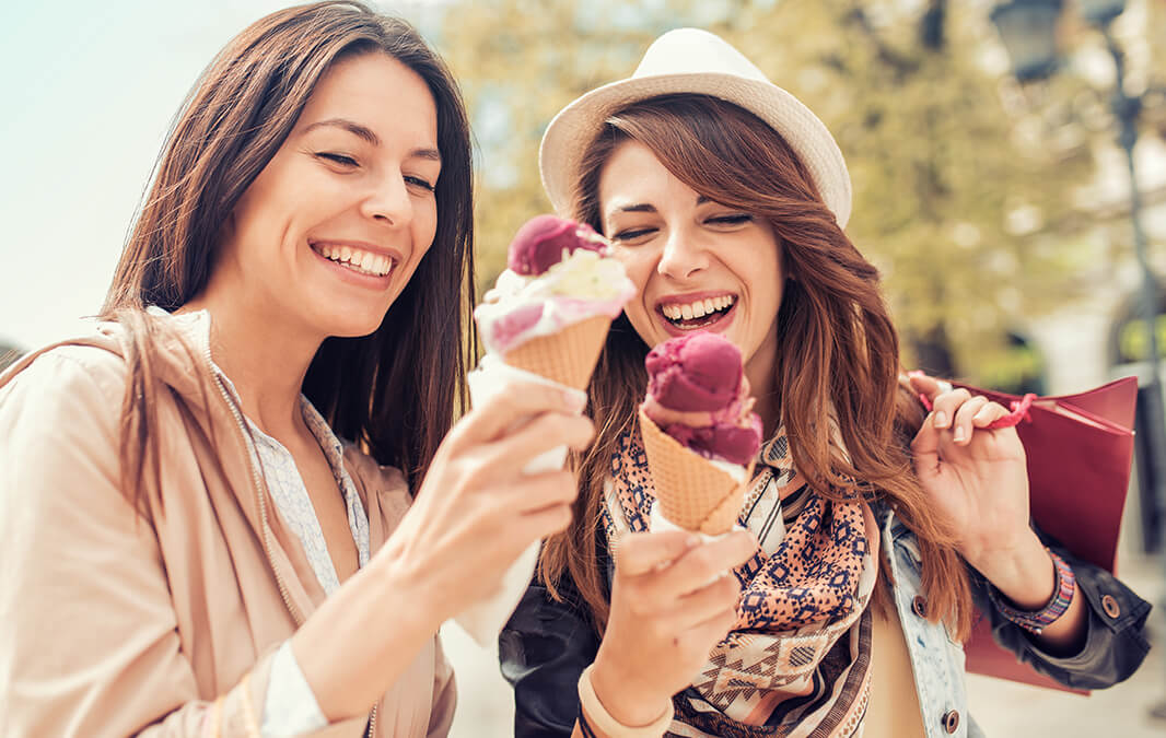 Two girls enjoying eating ice cream