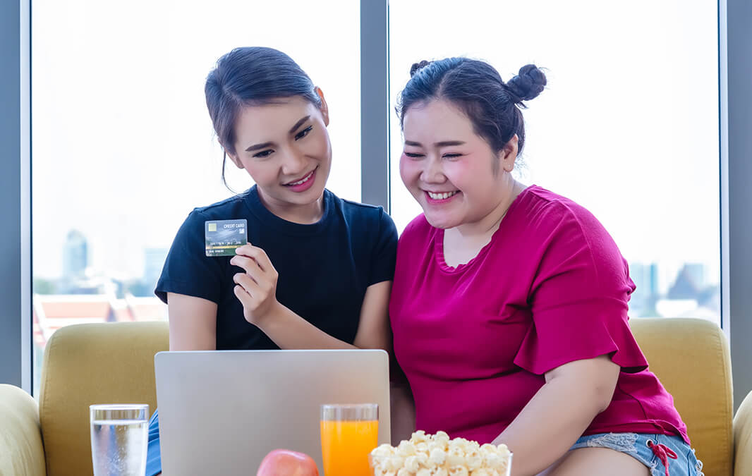two girls paying online with a credit card