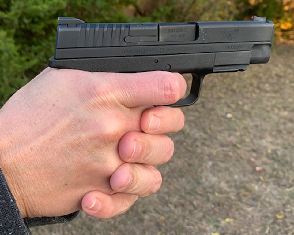 Hand holding small firearm index finger on trigger