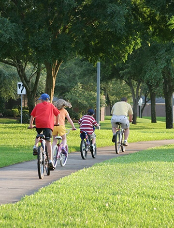 Bike riders on path surrounded by Tall Fescue grass
