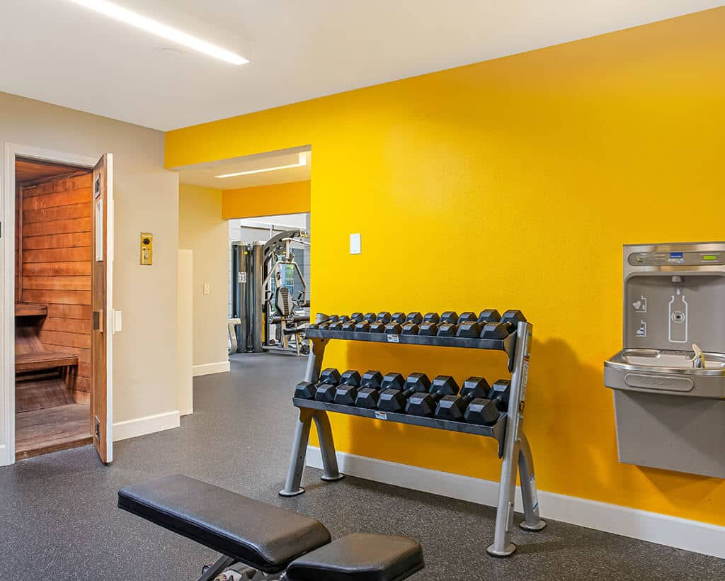 Yellow walled gym with water fountain and dumbells