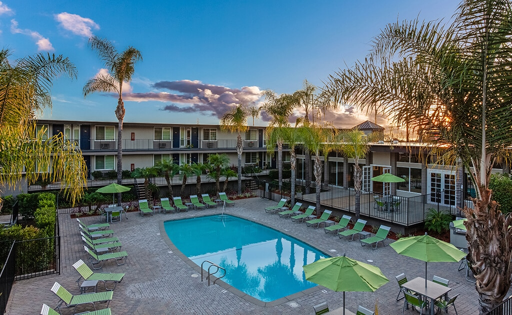 Resort style pool at Summerwood Apartment Homes with green lounge chairs and umbrellas