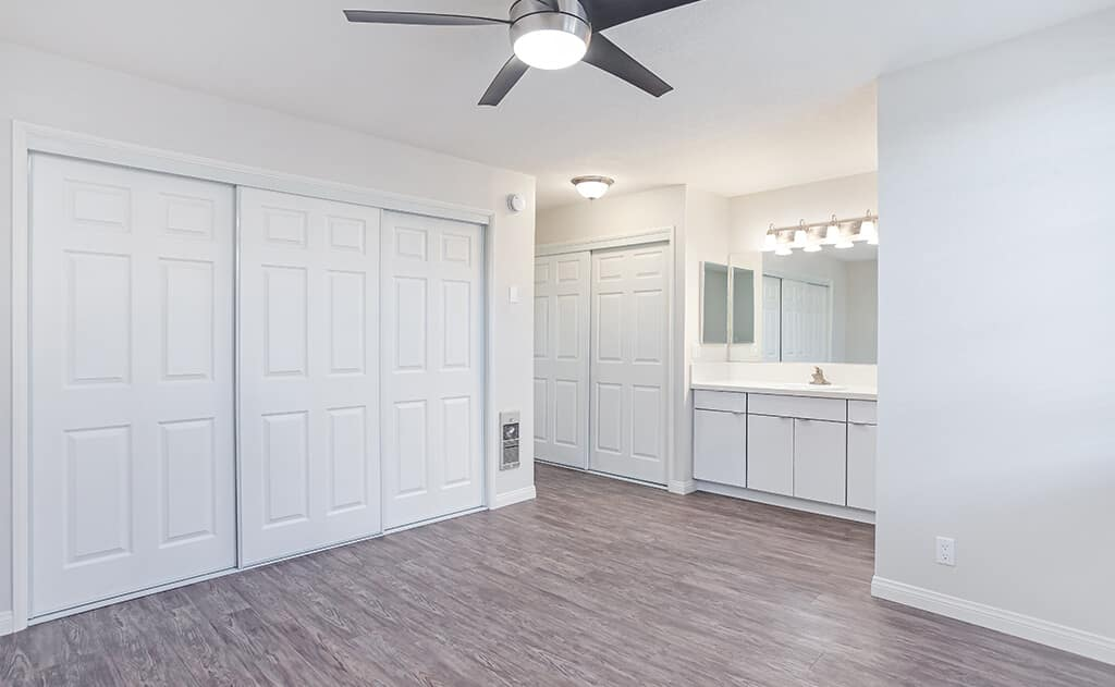 Empty bedroom with large closets and ceiling fan