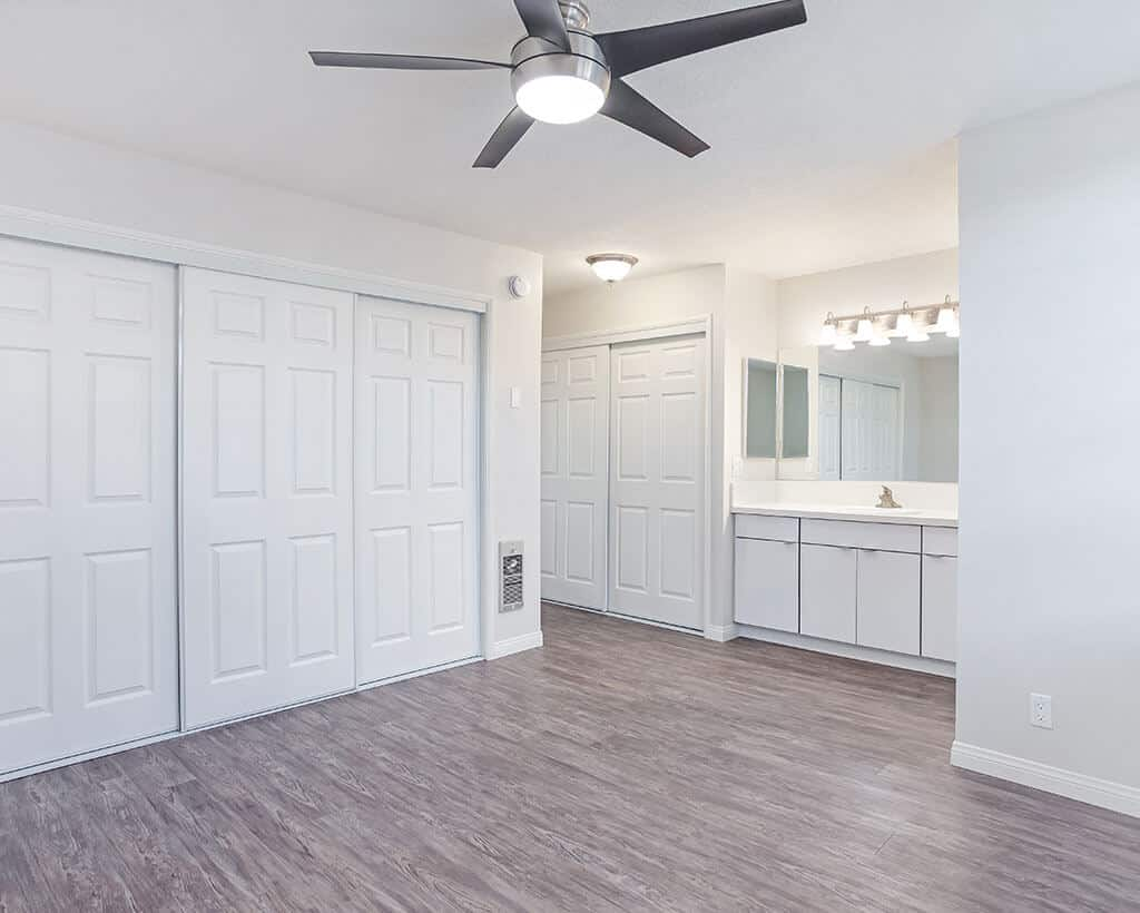 Bedroom with ceiling fan, closet, and sinks