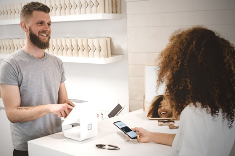 Bearded customer smiles while checking out on tablet