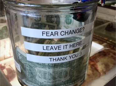 """Glass change jar with """"Fear Change? Leave it Here"""" label"""