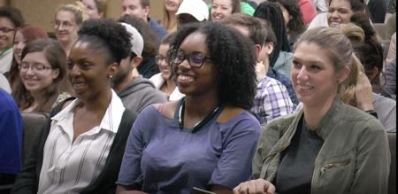 Group of young women listening to Keynote Speaker Vicki Hitzgesand smiling