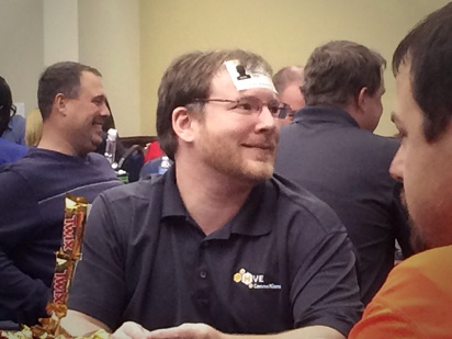 Man smiling with card on forehead during a workshop with keynote speaker Vicki Hitzges