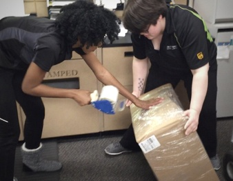 Female UPS workers taping box