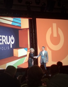 Keynote Speaker Vicki Hitzges on stage at Power Up conference shaking hands with male audience member