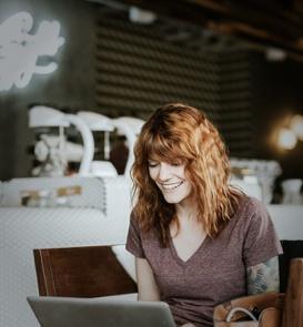 Smiling woman sitting at laptop