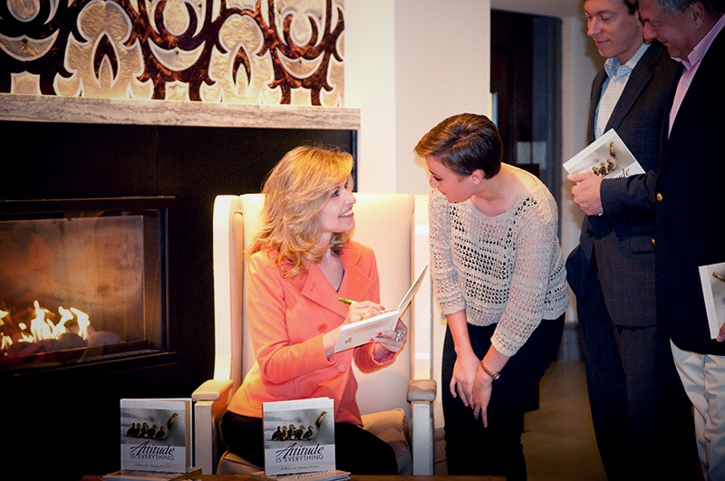 Author and Keynote Speaker Vicki Hitzges signs books for crowd in front of a big fireplaceoman