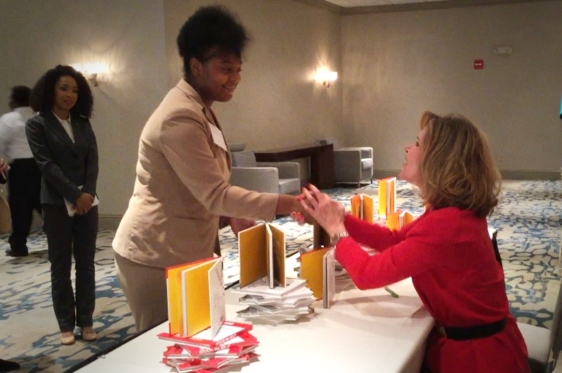 Keynote speaker Vicki Hitzges at book signing shakes hands with woman