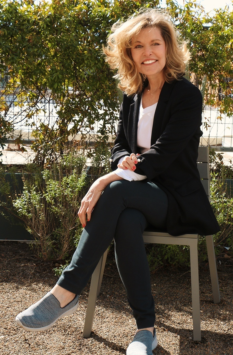 Keynote Speaker Vicki Hitzges smiles while sitting on bench in garden