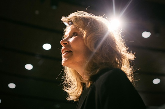 Keynote Speaker Vicki Hitzges low angle in auditorium with star light over her head