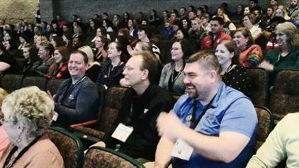 Large audience in auditorium laughing and enjoying Keynote Speaker Vicki Hitzges.