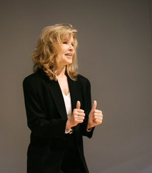 Keynote speaker Vicki Hitzges on gray stage with thumbs up