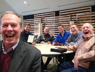 Group of men around table laughing
