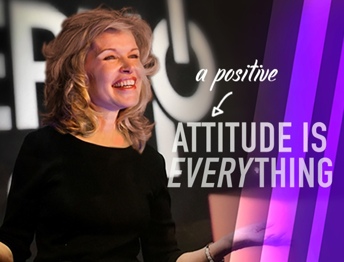 Keynote Speaker Vicki Hitzges on stage with A Positive Attitude is Everything text