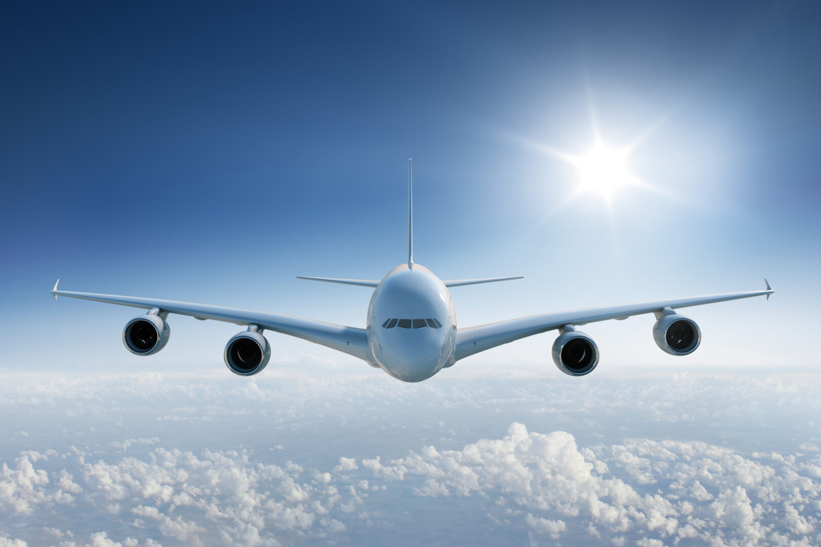 Big airplane flying above the clouds, towards the camera with the sun in blue sky