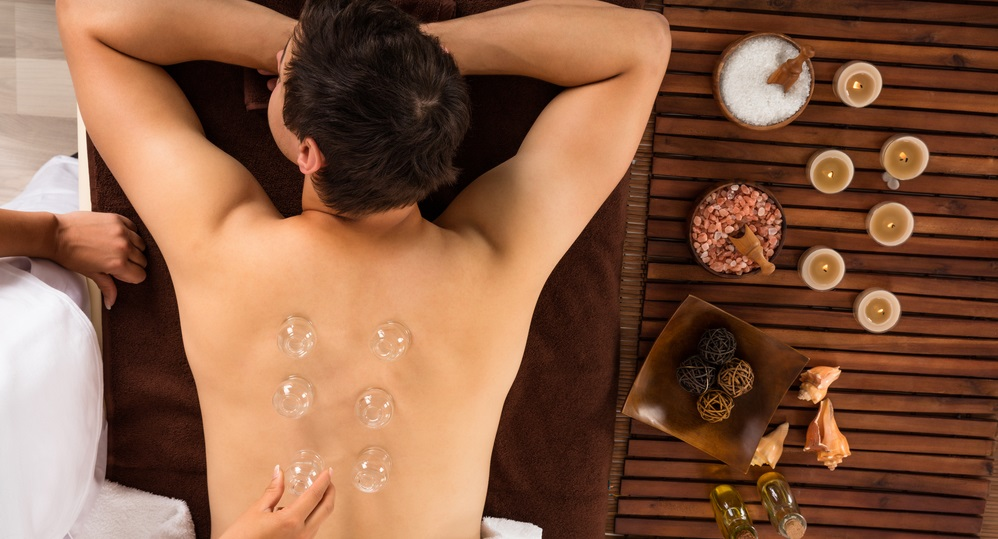 angle view of a relaxed young man receiving cupping treatment