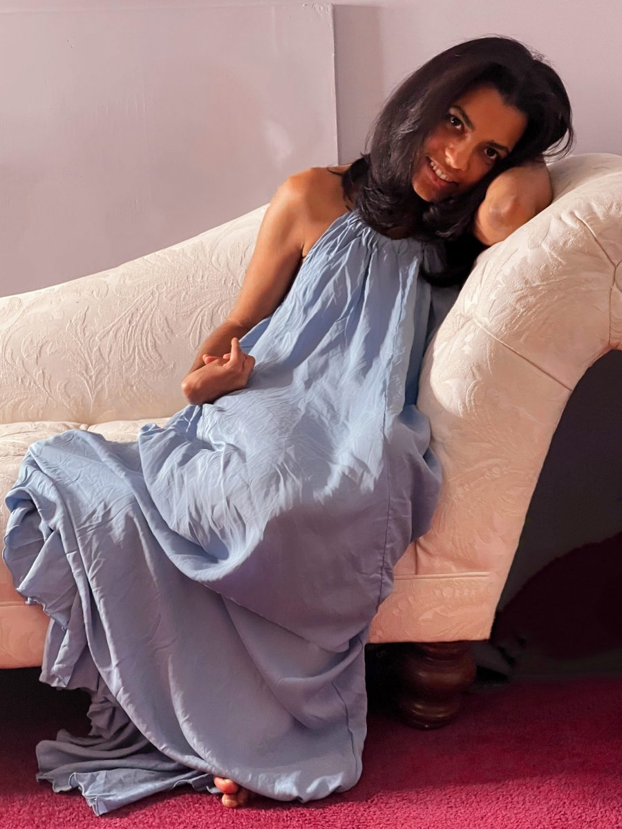 Brunette laying on a love site wearing a blue maxi dress and smiling while looking sideways and remembering that being single is not bad and it is about self-love.