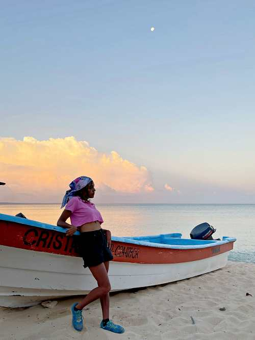 Sunrise with the Caribbean ocean as a background. Girl leaning against a fishing boat wearing black shorts and a pink crop top