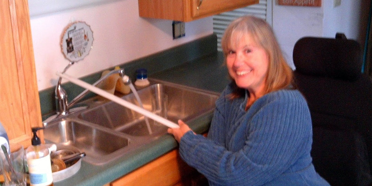 Joyce using her kitchen faucet modification