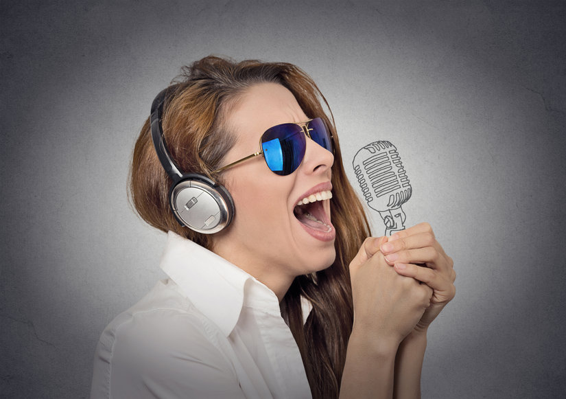 woman with sunglasses singing with microphone