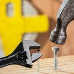 hammer and wrench on the wrong nail and screw