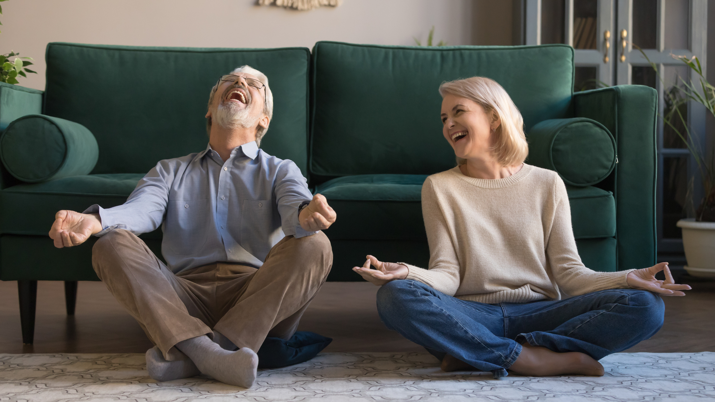 Laughing funny elderly spouses sitting in living room on floor in lotus position practice meditation distracted from yoga exercise joking feels overjoyed, healthy active lifestyle of retirees concept