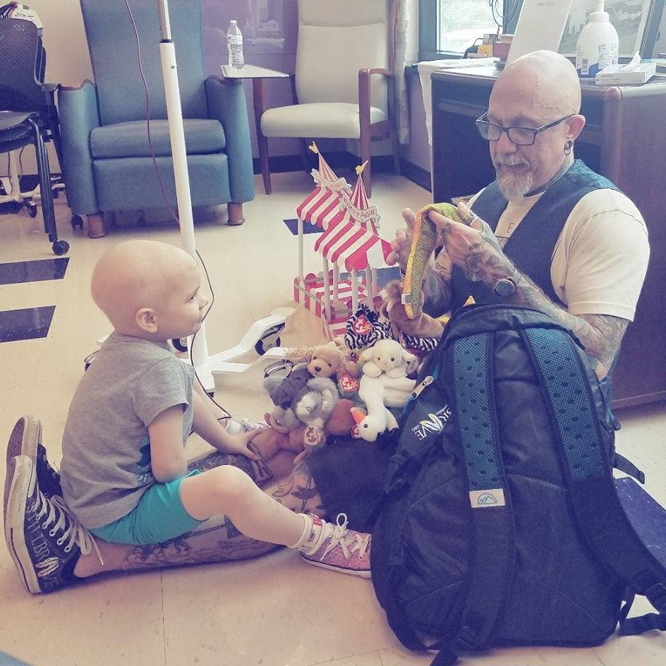 Tattoo Tom plays with a child in the hospital waiting room