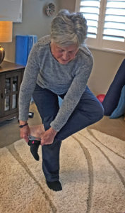 Joyce putting on sock while doing standing Figure 4 exercise move