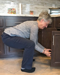 Joyce squatting move to get pots and pans on lowest shelves in kitchen