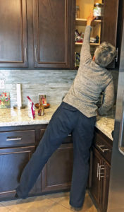 Joyce standing and stretching to reach into top cupboard
