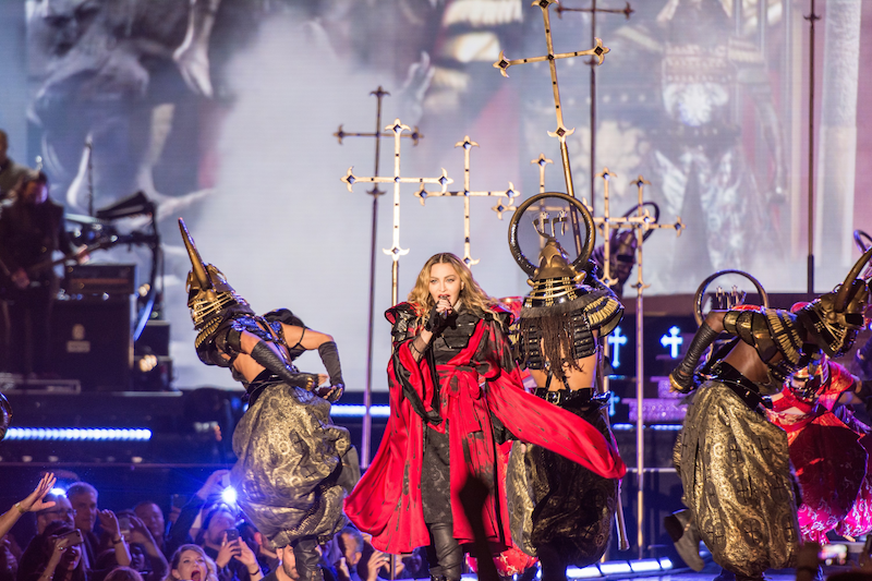 Madonna onstage singing in a red flowing cape with two Egyptian looking sarchophagi dancers. Taken live during her