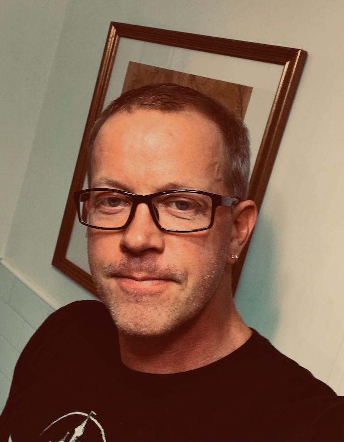 headshot of Roy Zornow in black shirt with glasses