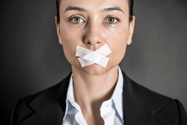 Young woman with tape on her mouth.