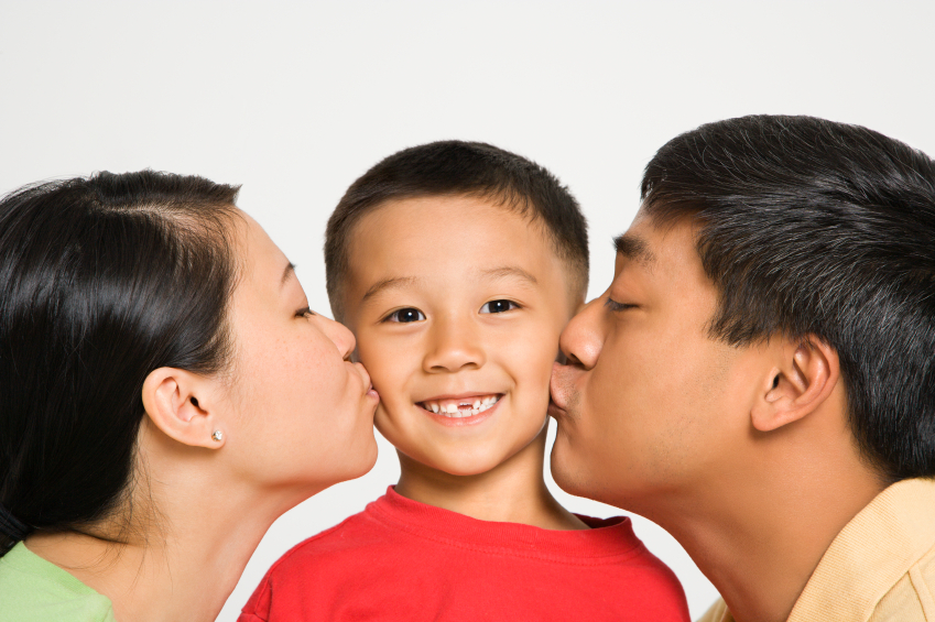 Asian mother and father kissing opposite cheeks of smiling son in front of white background.