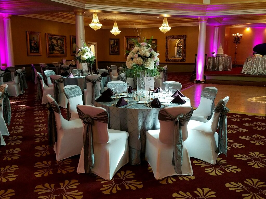 Steel Pintuck Tablecloths and Sashes with Eggplant Poly Napkins w/ White Spandex Chair Covers