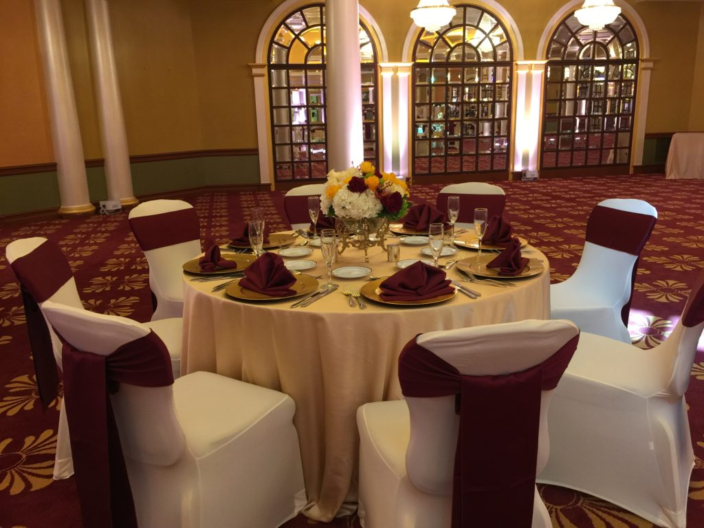 Champagne Majestic Tablecloth w/ Burgundy Satin Sashes and Napkins w/ White Spandex Chair Covers